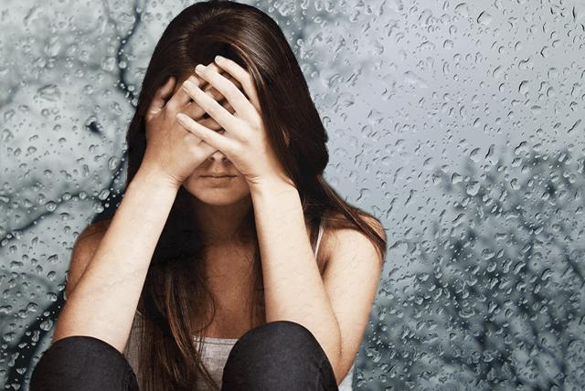 Сезонная депрессия девушки на фоне стекла в каплях дождя