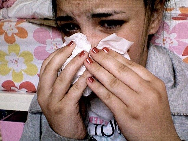 Девушка с аллергией утирает нос носовым платком