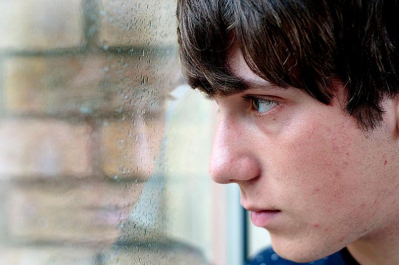 Парень, депрессивно смотрящий в окно