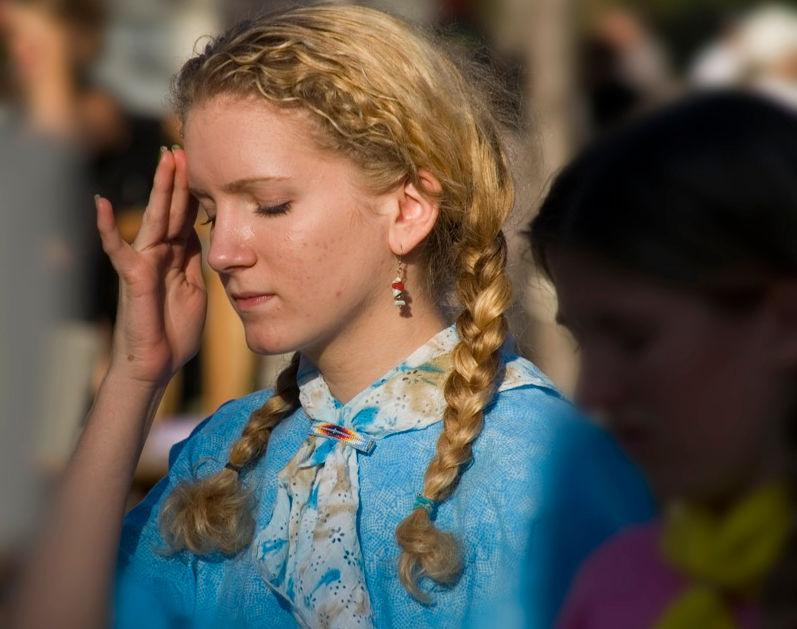 Девушка с головной болью в толпе