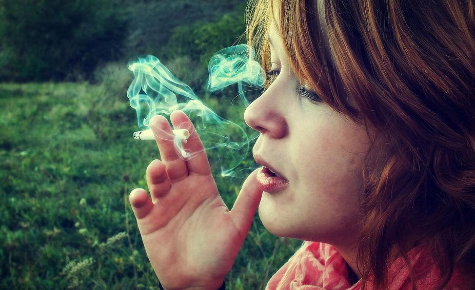 Женщина с дымящейся сигаретой в руке