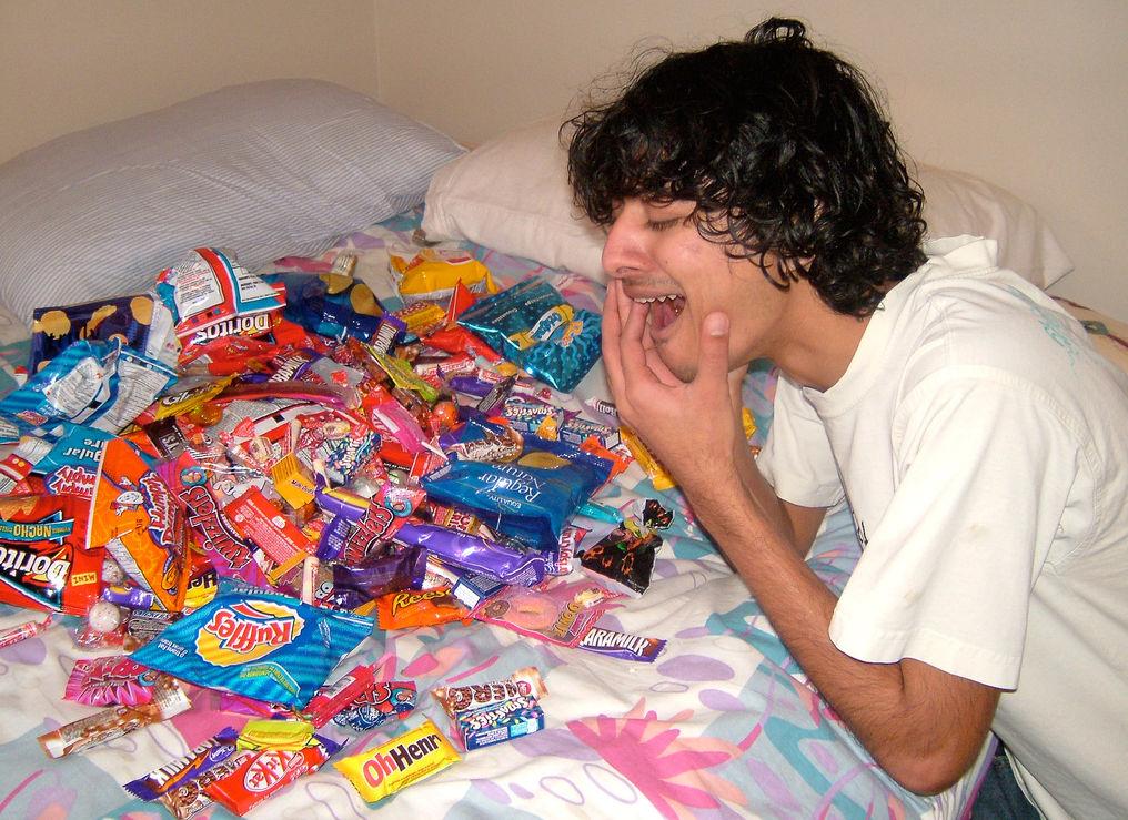 Мужчина с больным зубом над сладостями