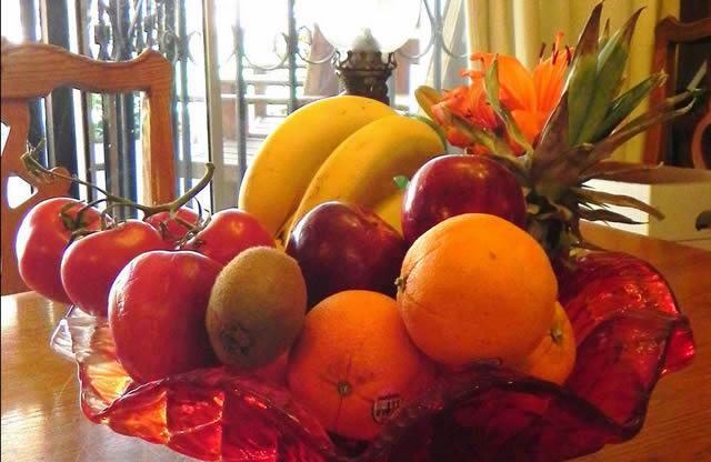 Разнообразные полезные фрукты в красной вазе на деревянном столе