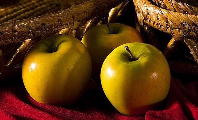 Сочные яблоки медового цвета на красной скатерти