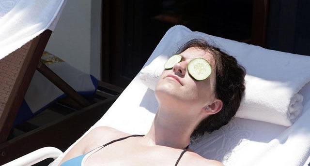 Дольки огурцов на глазах уставшей женщины