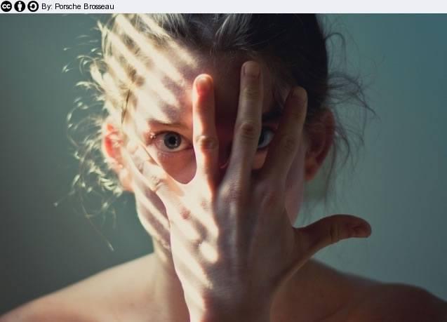 Девушка прикрывает лицо в страхе перед ярким солнечным светом
