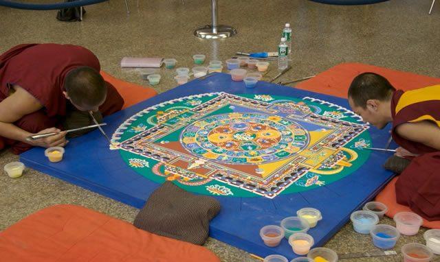 Тибетские монахи заняты созданием полотна мантры