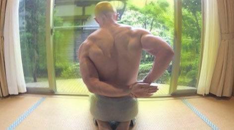 Мужчина с мускулистыми плечами выполняет упражнение на растяжку