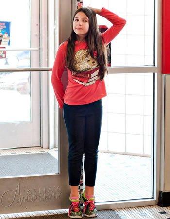 Девочка замеряет свой рост, встав на носки
